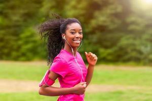 corredor de mulher afro-americana, movimentando-se ao ar livre - fitness, pesso foto