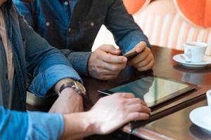 homens em um café com telefone e tablet foto