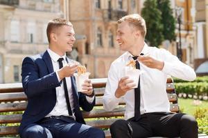 dois homens bonitos comendo macarrão chinês foto