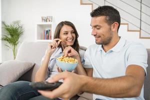 jovem casal com pipoca assistindo filme em casa