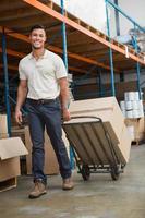 trabalhador de armazém, movendo caixas no carrinho
