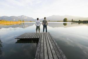 dois homens de pé em um píer. foto