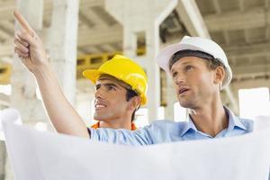 arquiteto masculino, explicando o plano de construção ao colega no canteiro de obras foto