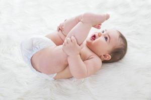 bebê feminino, deitado na pele de carneiro foto