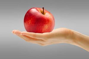 mão feminina com maçã vermelha foto