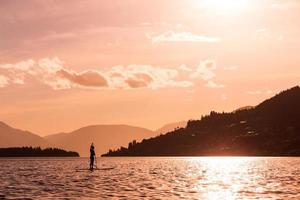 jovem fêmea rema um paddleboard