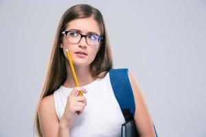 adolescente feminino pensativo, segurando o lápis foto