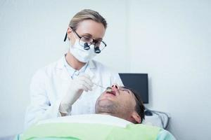 feminino dentista examinando mans dentes foto