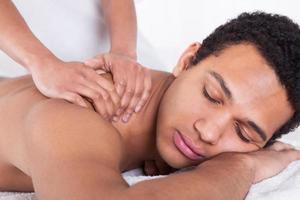 homem recebendo massagem da mão feminina foto