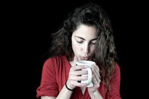 jovem fêmea segurando uma xícara de café foto