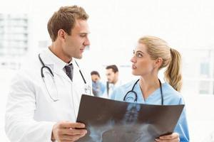 médicos masculinos e femininos, examinando o raio-x foto