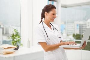 médica usando laptop no consultório médico foto