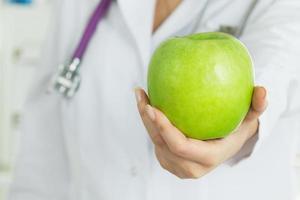 mão do médico feminino oferecendo maçã verde fresca foto