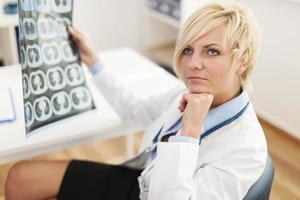 Médica pensativa com imagem de raio-x foto