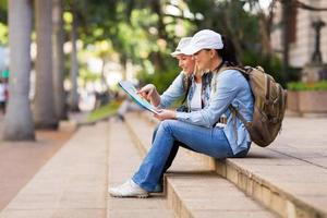 jovens turistas femininos olhando para o mapa