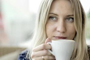mulher loira beber café no café foto