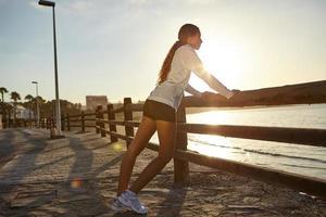 jovem atleta exercitando na costa foto