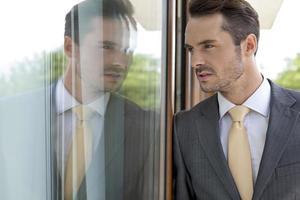 empresário pensativo, apoiando-se na porta de vidro