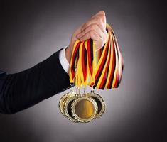 empresário segurando medalhas de ouro foto