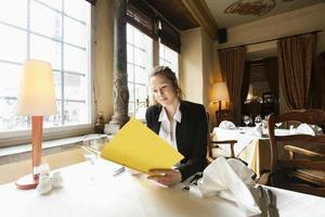 menu de leitura linda cliente na mesa do restaurante foto