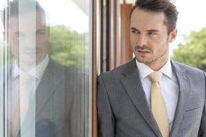 empresário, olhando para longe enquanto encostado na porta de vidro