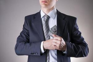 empresário com dinheiro em estúdio. conceito de corrupção. notas de cem dólares foto