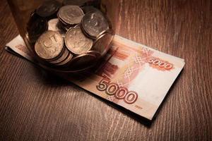 maço de notas de banco e um pote de vidro com moedas foto