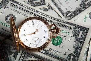 relógio de ouro e notas de dólar foto