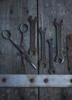 algumas chaves inglesas e tesouras com fundo de madeira foto