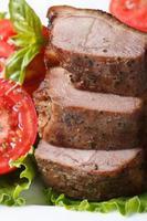 fatias de filetes de carne de pato assado com tomates verticais foto