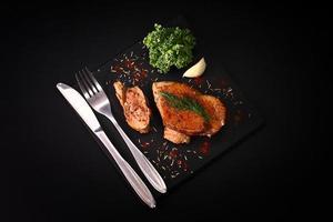 peito de pato assado suculento em uma mesa preta e talheres foto