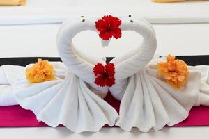 cisnes brancos feitos de toalhas na cama no hotel foto