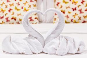 dois cisnes em forma de coração feitos de toalhas. foto