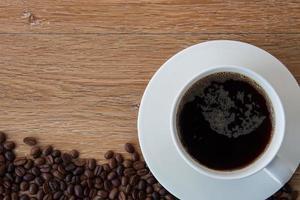xícara de café preto e grãos de café sobre fundo de madeira.
