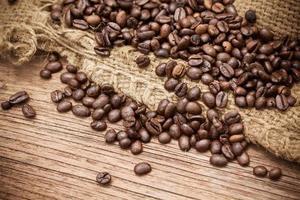grãos de café frescos em fundo madeira