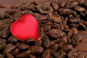 grãos de café e coração vermelho sobre fundo de madeira