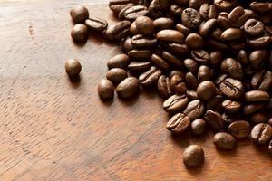 grãos de café sobre fundo madeira foto
