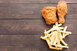 frango frito e batatas fritas em um fundo de madeira foto