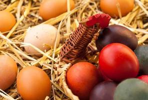ovos no feno e cesta tecida foto