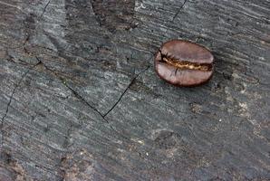Grão de café sobre fundo de madeira (queima de madeira) foto