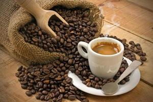 xícara de café e grãos na mesa de madeira