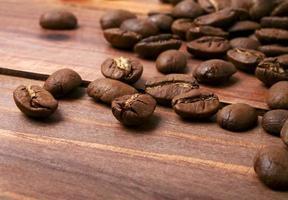 grãos de café em um fundo de madeira foto