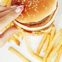 mãos de mulher com manicure segurando hambúrguer e batatas fritas isoladas foto
