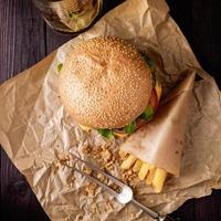 hambúrguer clássico e batatas fritas em cima da mesa.
