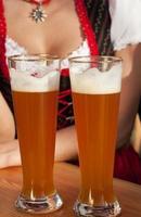 mulher em vestidos casuais bebendo cerveja de trigo foto