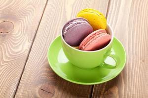 biscoitos de macaron colorido na xícara de café foto