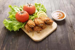 asas de frango frito no fundo de madeira foto