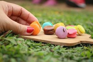 mão foram colhidos coloridos de macaron em uma bandeja marrom foto
