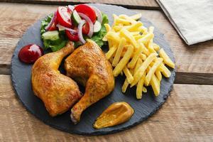 pernas de frango assado com batatas fritas e salada foto