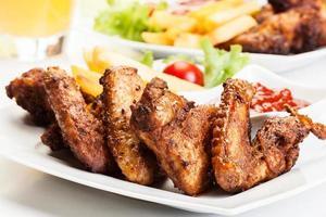 asas de frango com batatas fritas e molho picante foto